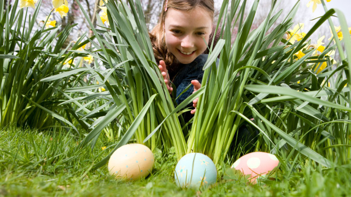 Landscaping tips for your easter egg hunt article image, a young girls peaks through lilly leaves at three eggs hidden behind them.